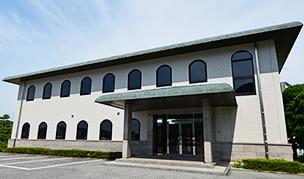 2階建て、白壁に上が丸い窓が特徴的な株式会社ozawaの本社