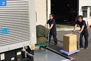 台車でトラックに荷物を積み込む社員